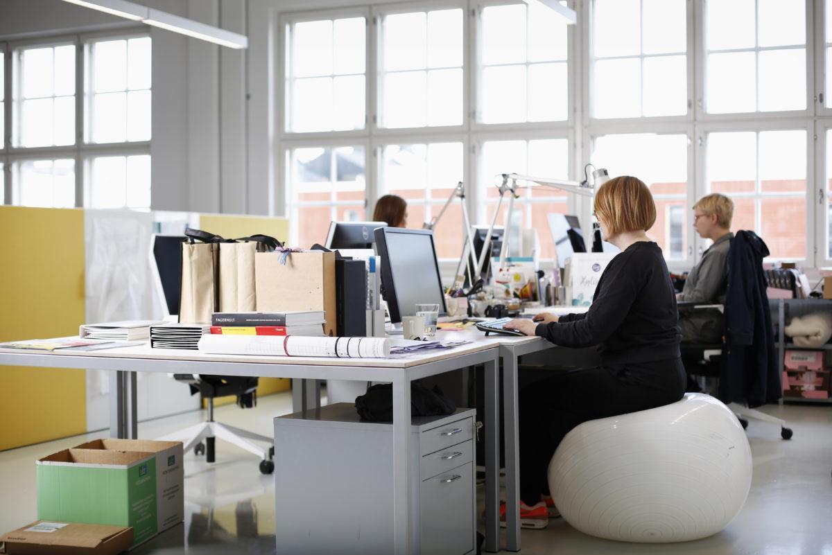 Ihmisiä istumassa työpisteillään koneiden ääressä avotoimistossa