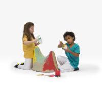 Lapset leikkivät Moby-tuolilla, joka on Mooki Mellon paperimassasta valmistama satulanmuotoinen tuoli.