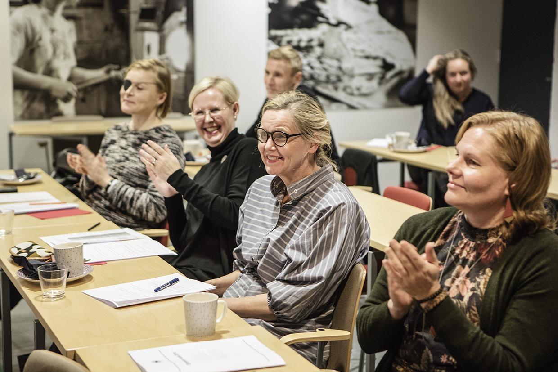 Iloisia ihmisiä kokouspöydän ääressä